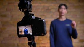 Tiro del primo piano videoblogger maschio coreano della registrazione della macchina fotografica di giovane che parla e che gestu stock footage