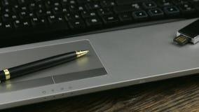 tiro del resbalador Lugar de trabajo con un ordenador portátil, una pluma y memoria USB, colocándose en un escritorio de madera almacen de metraje de vídeo