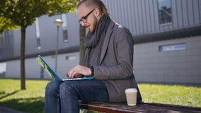 Tiro del retrato del hombre joven caucásico hermoso con una barba que se sienta en el banco con el ordenador portátil Estudiante  almacen de video