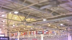 Tiro del techo adornado con las banderas multinacionales que cuelgan junto en el edificio de la exposición almacen de metraje de vídeo