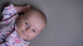 Tiro del top del primer de la muchacha recién nacida bonita que miente en el sofá y que mira hacia abajo atento metrajes