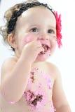 Tiro di moneta falsa del dolce: Neonata sudicia che mangia torta di compleanno! Fotografia Stock