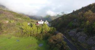 Tiro di Quadcopter di un livello della chiesa cristiana nelle montagne stock footage
