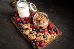 Tiro diagonal de cookies caseiros, de frutos da floresta e de um frasco do leite sobre a bandeja de madeira imagens de stock