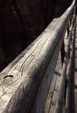 Tiro diagonal de la barandilla del puente de madera con el fondo oscuro del agua Imágenes de archivo libres de regalías