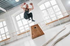 Tiro dinâmico do atleta masculino da aptidão que salta completamente na caixa quadrada no gym do crossfit imagens de stock royalty free