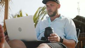 Tiro do baixo ângulo do homem de negócios relaxado feliz bem sucedido que usa o portátil que descansa na cadeira de sala de estar filme
