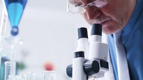 Tiro do baixo ângulo do químico que analisa os tubos com as amostras que olham então no microscópio video estoque
