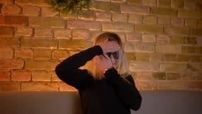 Tiro do close up do adolescente fêmea novo que olha um filme de ação 3D nos vidros na tevê e que obtém um jumpscare dentro na filme