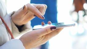 Tiro do close-up As mãos da mulher com o smartphone no shopping Natal Reflexão de remendos solares da luz filme