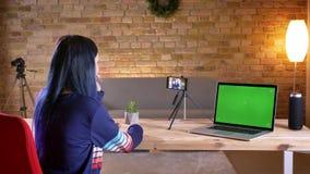 Tiro do close up do blogger video fêmea atrativo novo que flui no telefone que fala e que gesticula ao ter vídeos de arquivo