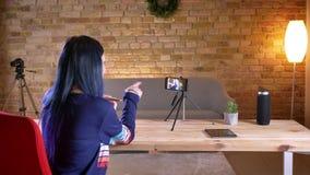 Tiro do close up do blogger video fêmea atrativo novo que flui no telefone que fala e que gesticula em um apartamento acolhedor vídeos de arquivo