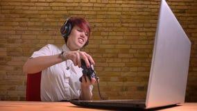 Tiro do close up do blogger video fêmea do moderno adolescente novo que joga jogos de vídeo no portátil com calor e ardor fotos de stock royalty free