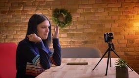 Tiro do close up do blogger video fêmea do moderno atrativo novo que fala ao fluir viva em gesticular da câmera vídeos de arquivo