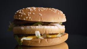 Tiro do close up do cheeseburger dobro suculento com rissóis saborosos alface e sésamo nos bolos vídeos de arquivo