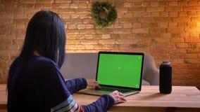Tiro do close up da consultação fêmea atrativa nova no portátil com a tela verde do croma dentro vídeos de arquivo