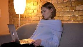 Tiro do close up da consultação fêmea bonita nova no portátil que senta-se no sofá e que está sendo relaxado na casa acolhedor video estoque