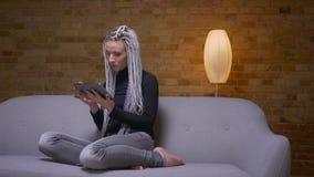 Tiro do close up da consultação fêmea do moderno caucasiano atrativo novo na mensagem da tabuleta no sofá dentro na vídeos de arquivo