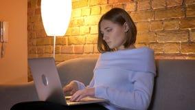 Tiro do close up da datilografia fêmea caucasiano nova no portátil que olha a câmera e que sorri ao sentar-se no sofá vídeos de arquivo
