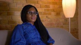 Tiro do close up da fêmea afro-americano adulta que olha um filme de terror 3D na tevê e que é assento assustado no sofá filme