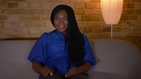 Tiro do close up da fêmea afro-americano adulta que olha uma comédia na tevê e que ri alegremente o assento no sofá video estoque