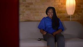 Tiro do close up da fêmea afro-americano adulta que olha uma comédia na tevê e que ri felizmente o assento no sofá dentro filme