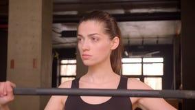 Tiro do close up da fêmea atrativa nova do atleta que anda e que prepara-se para levantar peso dentro no gym filme