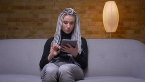 Tiro do close up da fêmea caucasiano atrativa nova do moderno que usa a tabuleta e rindo felizmente o assento no sofá video estoque