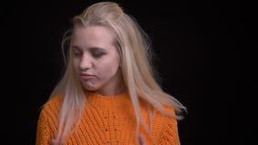 Tiro do close up da fêmea caucasiano bonita nova com o cabelo louro longo que acena sua cabeça no símbolo do desacordo na parte d filme