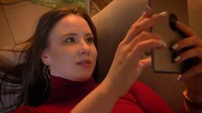 Tiro do close up da fêmea caucasiano bonita nova que datilografa na tabuleta ao encontrar-se no sofá dentro video estoque