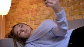 Tiro do close up da fêmea caucasiano bonita nova que encontra-se em seu lado no sofá e que toma selfies no telefone que é vídeos de arquivo