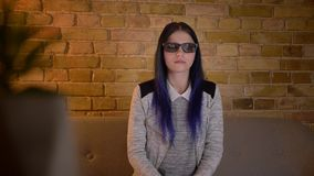 Tiro do close up da fêmea caucasiano bonita nova que olha um filme de ação 3D na tevê nos vidros e que obtém o assento surpreso filme