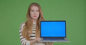 Tiro do close up da fêmea caucasiano bonita nova que usa o portátil e mostrando a tela azul à câmera com fundo filme
