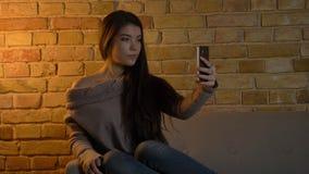 Tiro do close up da fêmea caucasiano bonito nova que toma selfies no telefone ao descansar no sofá na casa acolhedor dentro imagem de stock royalty free