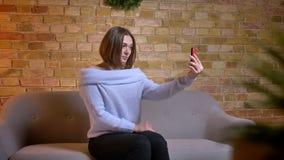 Tiro do close up da fêmea caucasiano bonito nova que toma selfies no telefone que levanta e que fixa seu cabelo ao sentar-se no filme