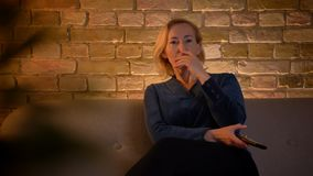 Tiro do close up da fêmea caucasiano do eldery que olha um filme de ação na tevê que está sendo excitada ao sentar-se no sofá video estoque