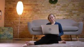 Tiro do close up da fêmea caucasiano do eldery que olha um filme no portátil com excitamento ao sentar-se no assoalho video estoque