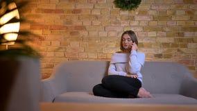 Tiro do close up da fêmea caucasiano encantador nova que tem uma conversação no telefone que senta-se no sofá na casa acolhedor vídeos de arquivo