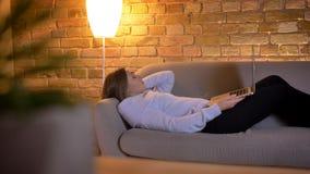 Tiro do close up da fêmea caucasiano nova que lê um ebook usando a tabuleta ao encontrar-se no sofá na casa acolhedor dentro video estoque