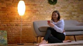 Tiro do close up da fêmea caucasiano nova que usa o telefone que senta-se no tapete acolhedor e que inclina-se no sofá atrás dela vídeos de arquivo