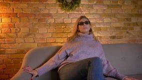 Tiro do close up da fêmea loura caucasiano adulta que olha um filme 3D na tevê nos vidros 3D ao sentar-se no sofá filme