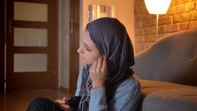 Tiro do close up da fêmea muçulmana atrativa nova nas vibrações usando o telefone ao sentar-se no assoalho na entrada em filme