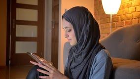 Tiro do close up da fêmea muçulmana atrativa nova no hijab que datilografa no telefone ao sentar-se no assoalho na entrada vídeos de arquivo