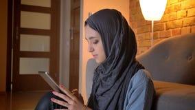Tiro do close up da fêmea muçulmana atrativa nova no hijab que datilografa no telefone ao sentar-se no assoalho na entrada video estoque