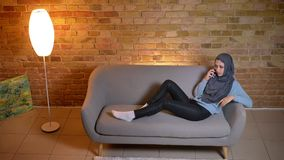 Tiro do close up da fêmea muçulmana atrativa nova que tem um descanso do telefonema laidback no sofá dentro na casa acolhedor filme