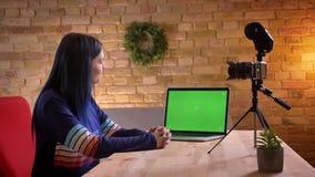 Tiro do close up da fluência video do blogger do moderno fêmea caucasiano adolescente novo viva usando a câmera e o portátil vídeos de arquivo