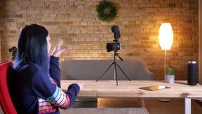 Tiro do close up da fluência video fêmea caucasiano atrativa nova do blogger viva e da fala alegremente na câmera e video estoque