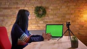 Tiro do close up da fluência video fêmea na moda atrativa nova do blogger viva na câmera usando o portátil com verde video estoque