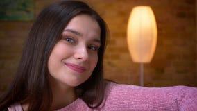 Tiro do close up da menina caucasiano moreno bonito nova que olha a câmera e que sorri felizmente sentando-se no sofá em um acolh video estoque