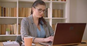 Tiro do close up da mulher de negócios caucasiano bem sucedida nova nos vidros usando o portátil no escritório da biblioteca dent filme